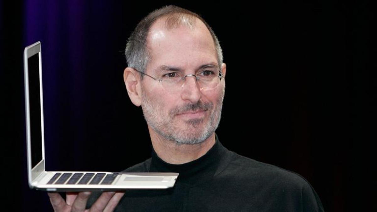 Steve Jobs holding a macbook air
