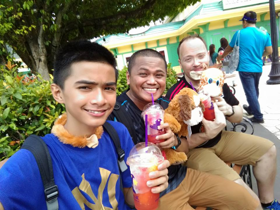 3 men slurping cold drink in a theme park