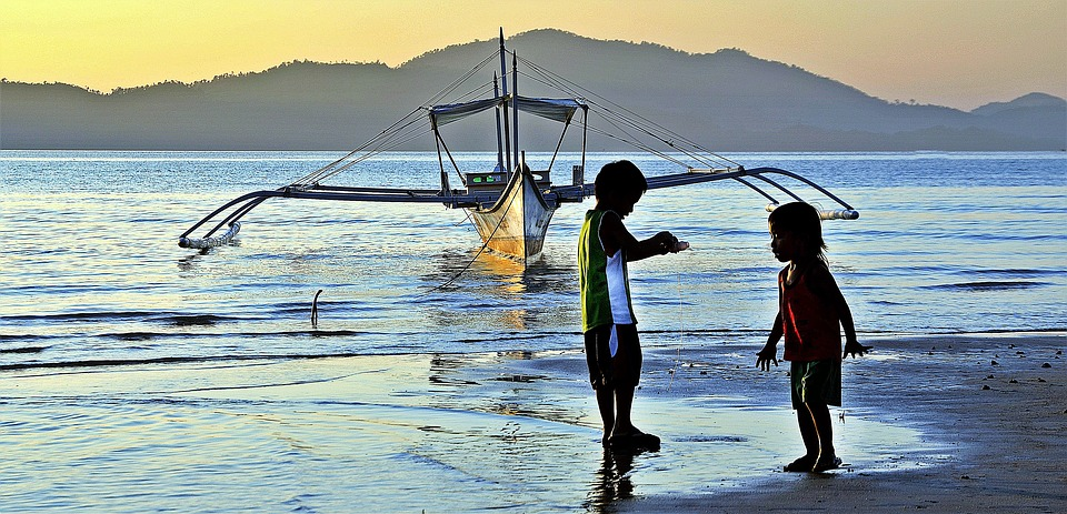 Kids playing beside a boat overlooking the sea