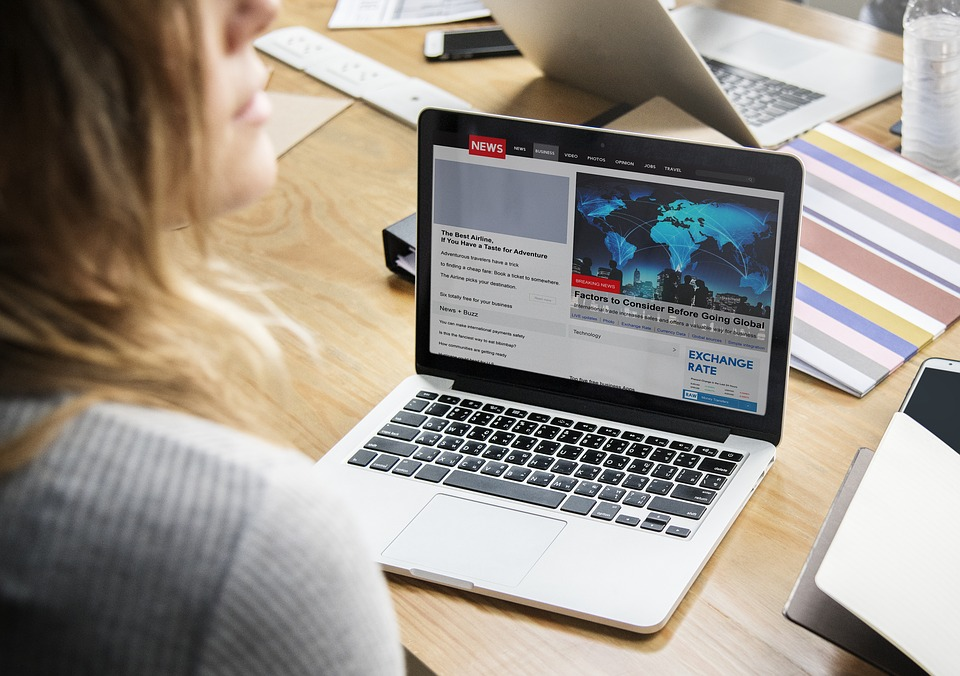 Young lady reading latest news on a laptop