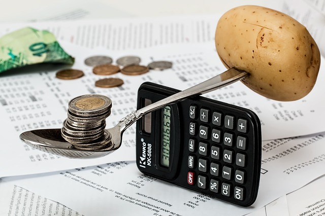 Coins and Potato spoon Balancing on a calculator