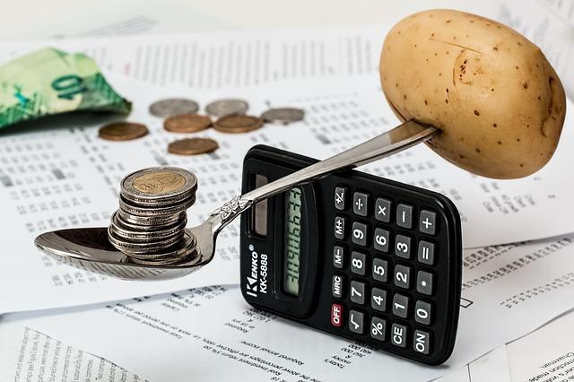 Coins and Potato spoon Balancing on a calculator