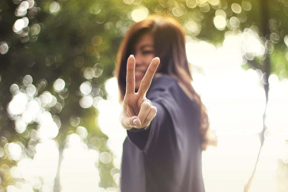 Smiling young lady with peace sign