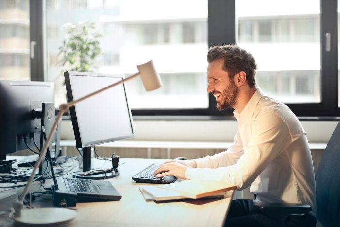 Man Smiling while working on desktop